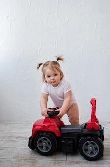 Petite fille monte une voiture rouge