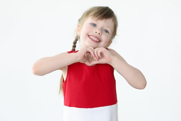 Petite fille montrant la forme du coeur avec ses mains
