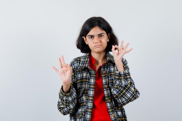 Petite fille montrant un geste correct en chemise, veste et semblant ravie. vue de face.