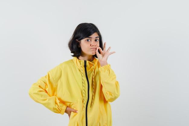 Petite fille montrant le geste de la fermeture éclair en sweat à capuche jaune et regardant prudente, vue de face.