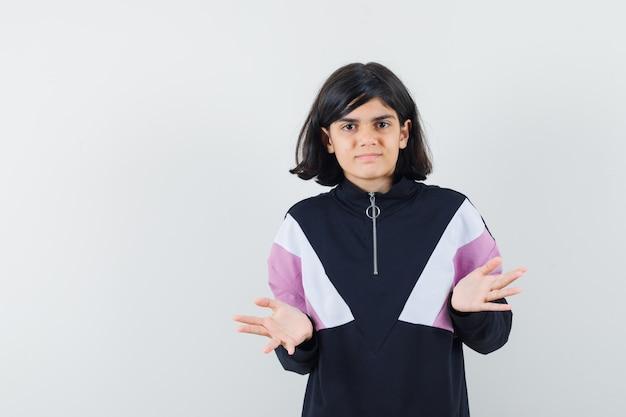 Petite fille montrant un geste impuissant en chemise et à la confusion. vue de face.