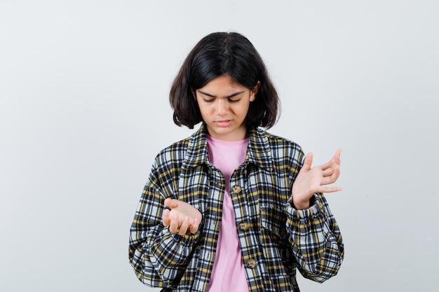 Petite fille montrant un geste impuissant en chemise, veste et l'air mécontent. vue de face.