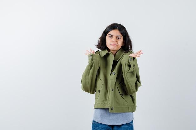 Petite fille montrant un geste impuissant en manteau, t-shirt, jeans et l'air confiant, vue de face.