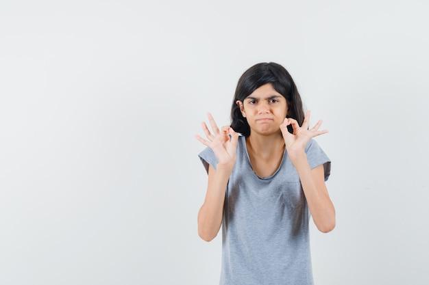 Petite fille montrant le geste ok en t-shirt et à la confusion. vue de face.