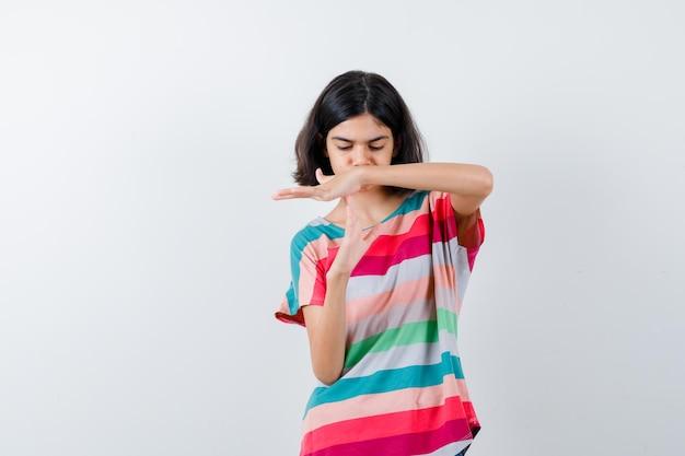 Petite fille montrant un geste de pause en t-shirt, jeans et l'air concentré. vue de face.