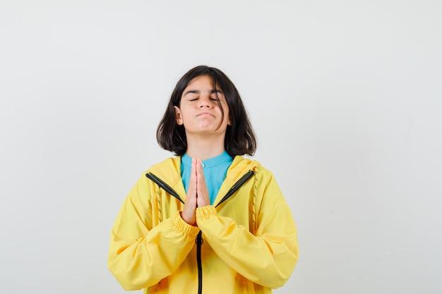 Petite fille montrant les mains jointes dans un geste de plaidoirie en chemise, veste et à l'air plein d'espoir, vue de face.