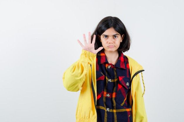 Petite fille montrant la paume en chemise à carreaux, veste et semblant sérieuse. vue de face.