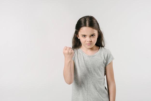 Petite fille montrant le poing en studio