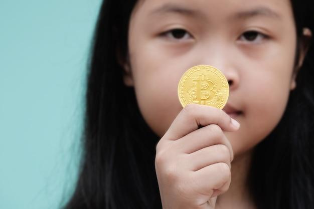 Petite fille montre or bitcoin en studio