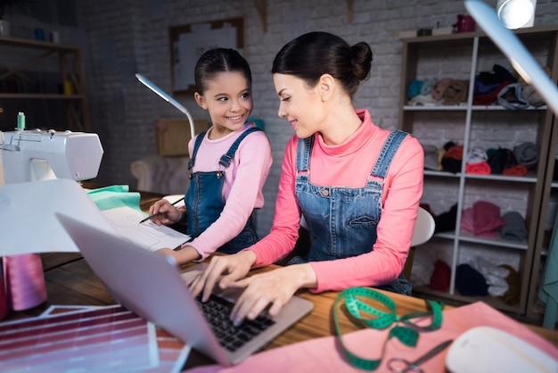 Petite fille montre un schéma de vêtements à une femme adulte.