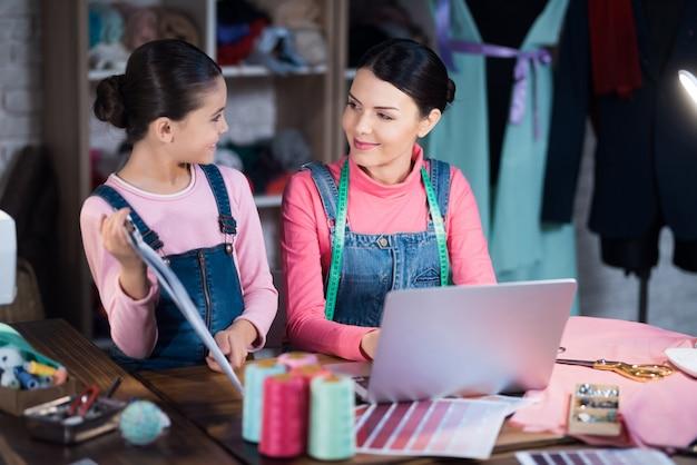 Petite fille montre un schéma de vêtements à une femme adulte