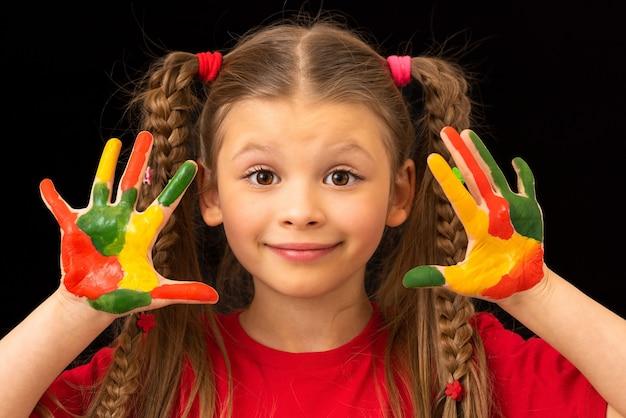 Une petite fille montre ses mains tachées de peinture à la gouache.
