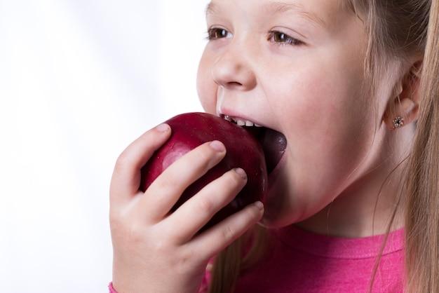Petite fille mord une grosse pomme rouge sur un mur blanc