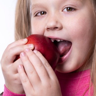 Une petite fille mord une grosse pomme rouge