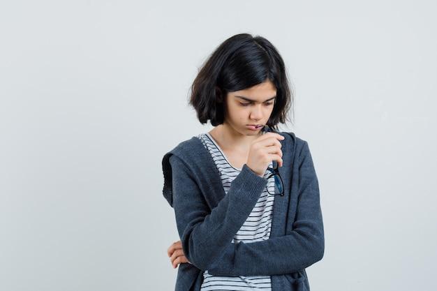 Petite fille mordant des lunettes en t-shirt, veste et à la déprimée.
