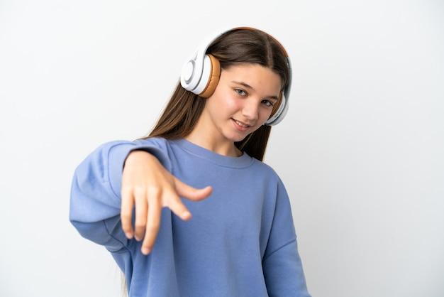 Petite fille sur mur blanc isolé, écouter de la musique
