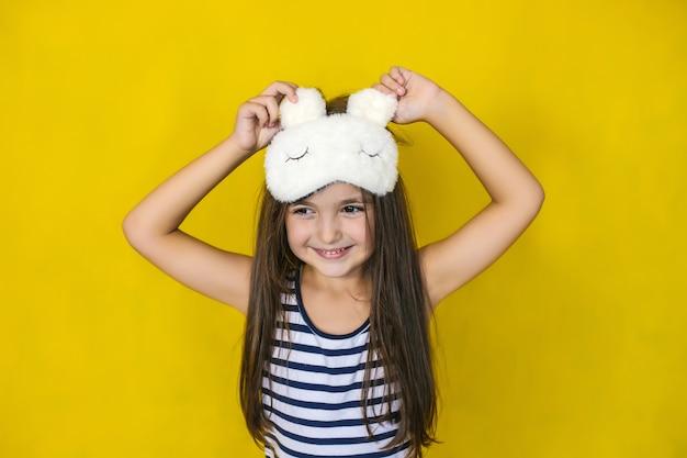 Une petite fille sur un mur jaune vif portant un masque de sommeil accessoire de mode.