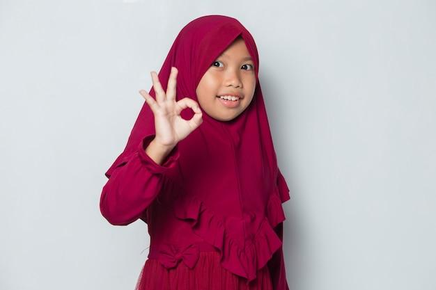Petite fille musulmane asiatique portant le hijab avec un geste de signe ok tombant