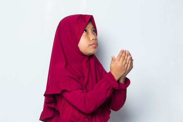 Petite fille musulmane priant par ouvrir son bras isolé sur fond blanc