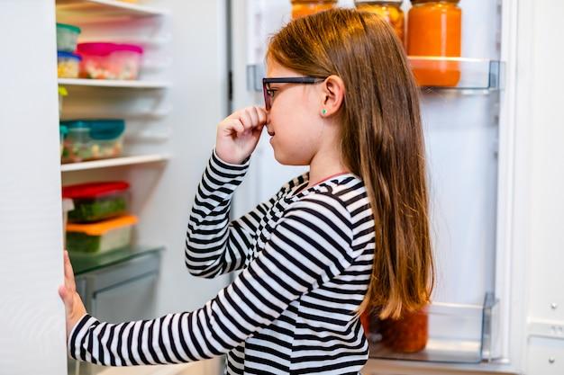 La petite fille n'aime pas les odeurs de légumes du réfrigérateur.