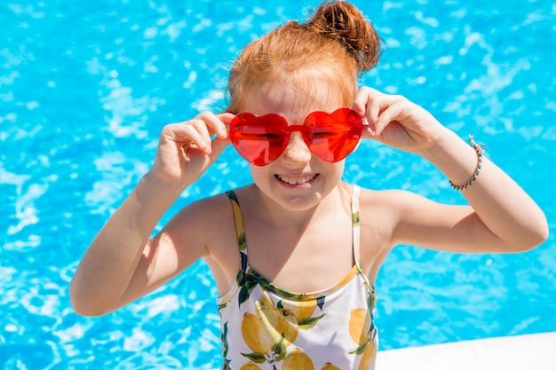 Petite fille nageant dans la piscine en été