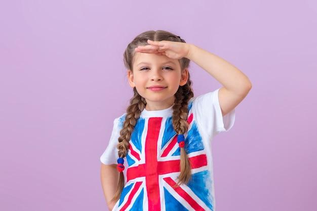 Une petite fille avec des nattes et une image du drapeau anglais regarde au loin.