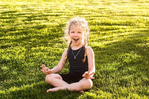 Petite fille avec des nattes souriant tout en faisant du yoga dans le parc