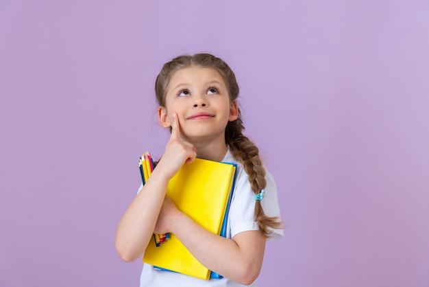 Une petite fille avec des nattes sur la tête tient plusieurs livres et crayons.