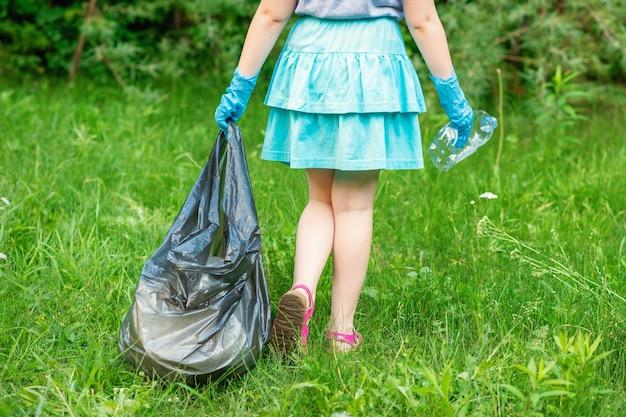 Petite fille nettoie les déchets en plastique sur l'herbe verte dans le parc