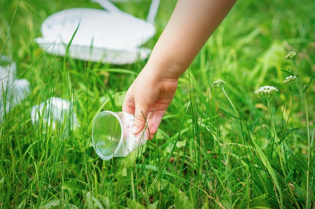 La petite fille nettoie les ustensiles en plastique