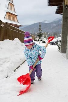 Petite fille nettoyant la neige de la cour, pologne, zakopane
