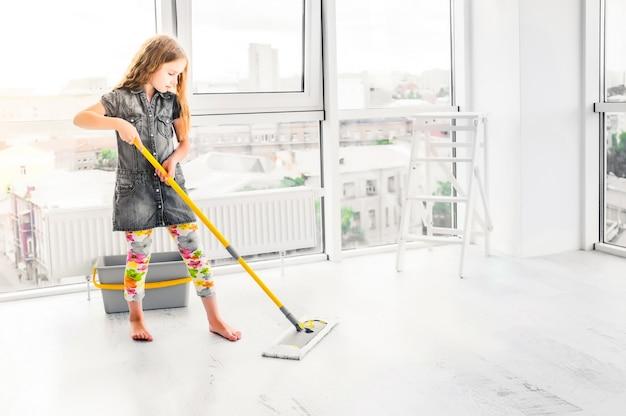 Petite fille nettoyant le sol dans la chambre