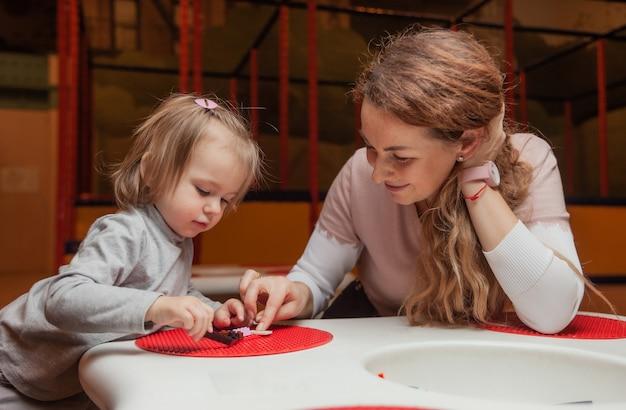 Petite fille avec une nounou joue des briques jouets à table dans un centre de divertissement pour enfants