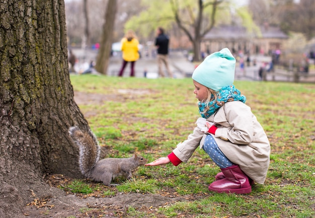 Petite fille nourrit un écureuil à central park, new york, amérique