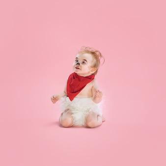 Petite fille nouveau-née portant un costume d'halloween sur fond de studio rose