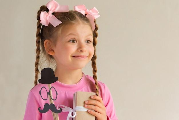 Une petite fille offre un cadeau pour la fête des pères.