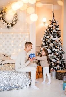 Petite fille offre un cadeau à son père. maisons sur fond d'arbre de noël.