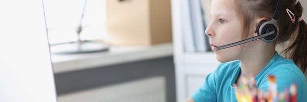Petite fille à l'ordinateur dans les écouteurs avec microphone travaille à l'ordinateur.