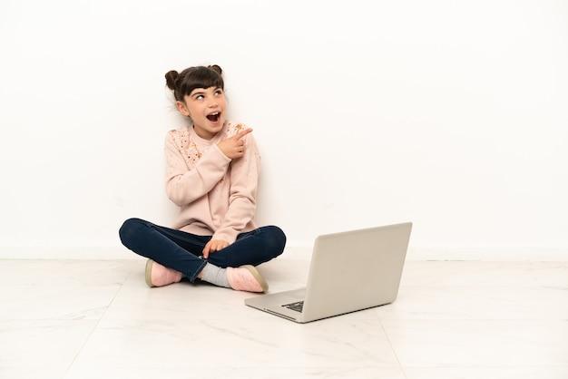 Petite fille avec un ordinateur portable assis sur le sol dans l'intention de réaliser la solution tout en levant un doigt