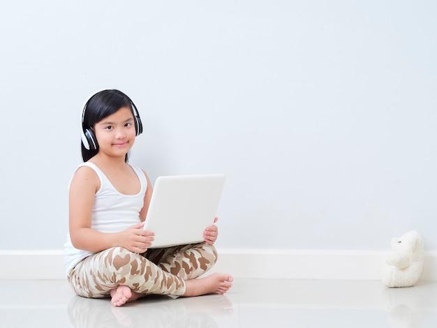 Petite fille avec ordinateur portable assis sur le sol.