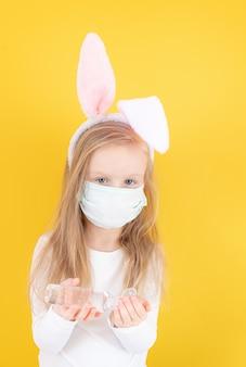 Petite fille avec des oreilles de lapin et un masque médical à l'aide d'un désinfectant pour les mains