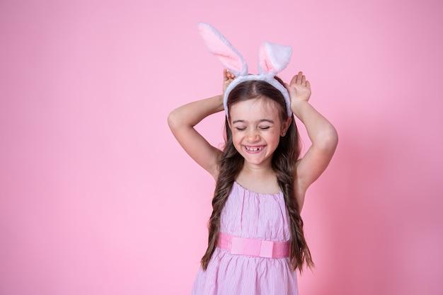 Petite fille avec des oreilles de lapin de pâques posant sur un studio rose