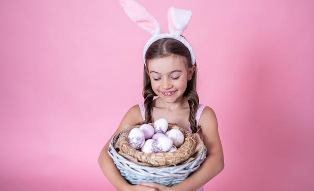 Petite fille avec des oreilles de lapin de pâques posant tenant un panier avec des oeufs de pâques festifs sur rose