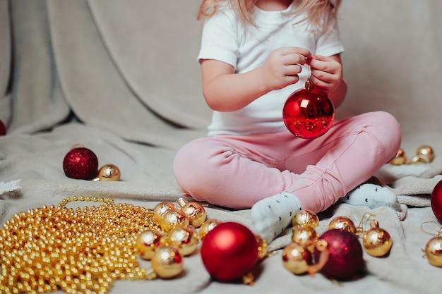Petite fille avec des ornements de noël autour.