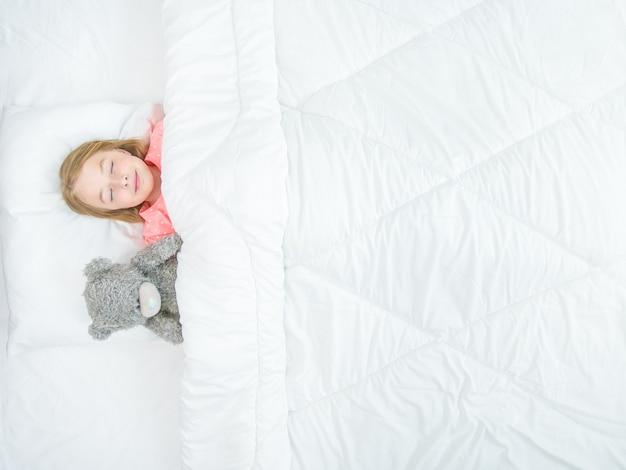 La petite fille avec un ours en peluche dormant sur le lit. vue d'en-haut