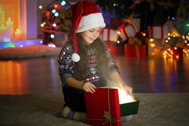 Petite fille ouvrant le cadeau de noël dans le salon