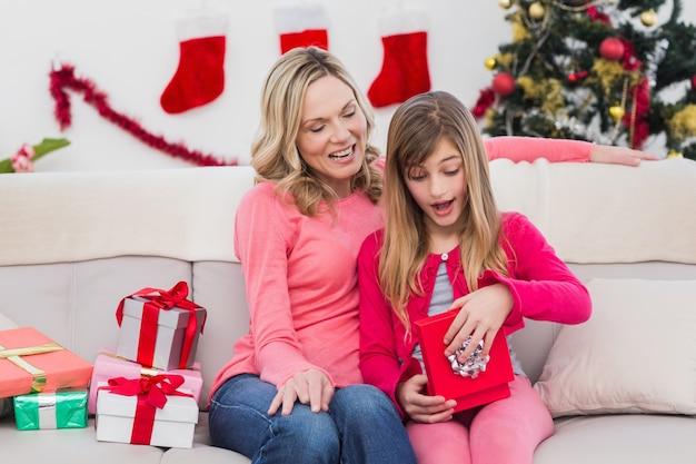 Petite fille ouvrant un cadeau à noël avec la mère