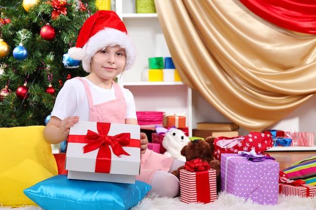 Une petite fille ouvre un cadeau dans une pièce décorée de façon festive