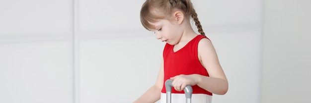 La petite fille ouvre le concept de voyage et de vols d'enfants de valise jaune