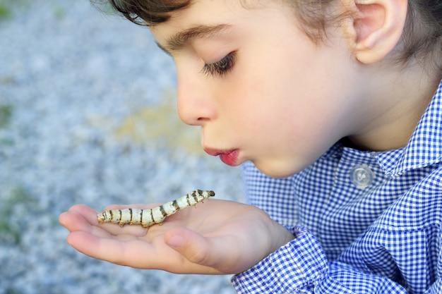 Petite fille palying avec ver à soie dans les mains